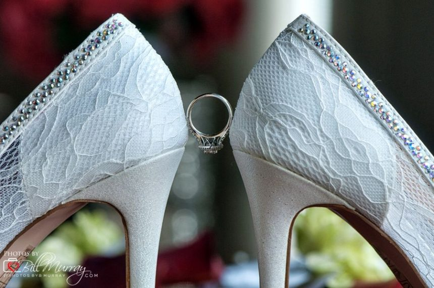 brides shoes with ring in between at wedding