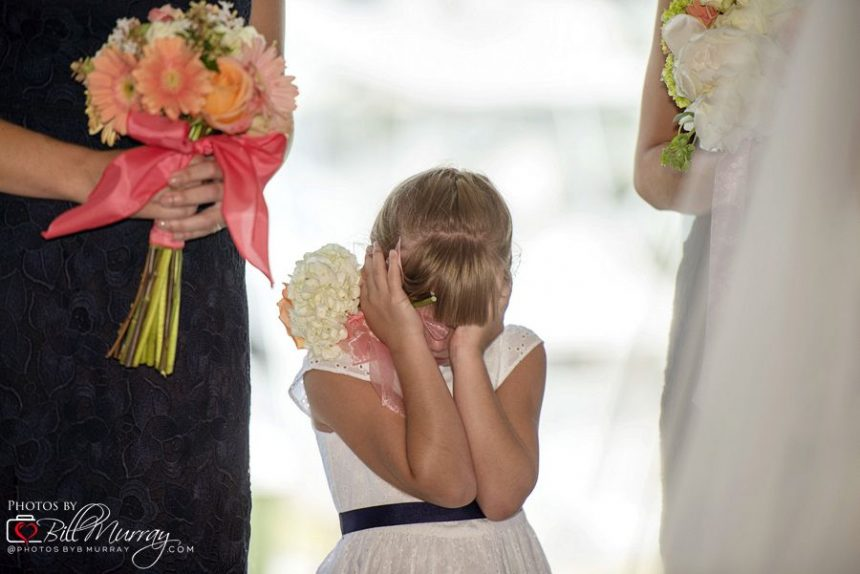 flower girl covers her eyes at kiss during ceremony
